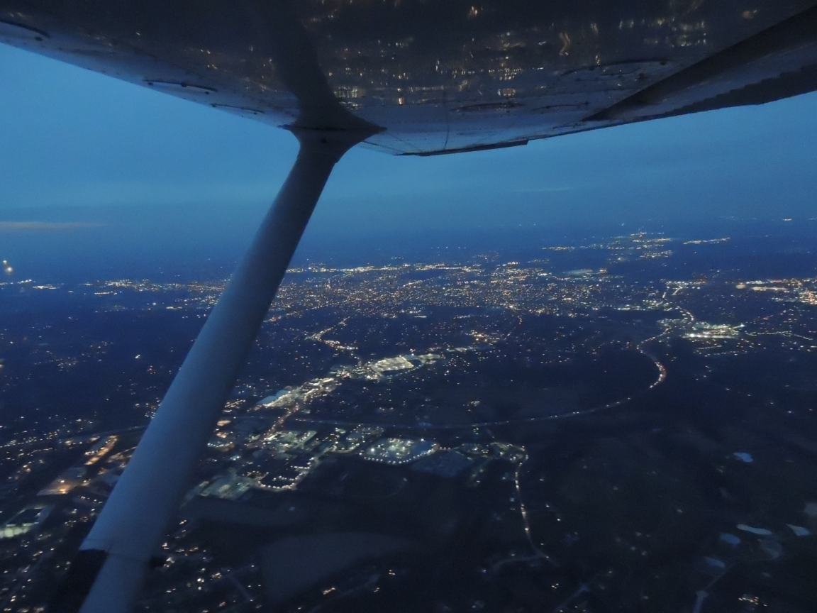 City lights reflecting on our wing